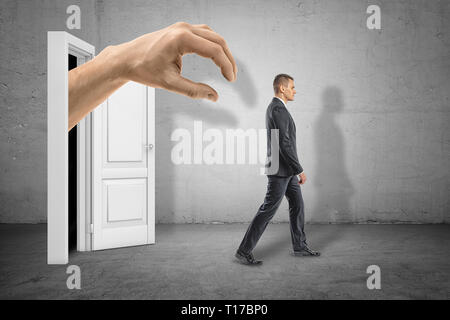 Vue latérale de la grande main de l'homme sortant de l'obscurité sur la porte blanche et prêt à prendre peu d'affaires qui est de s'éloigner et de ne pas voir la main. Banque D'Images