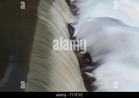 Flou de mouvement d'une chute d'eau sereine splashing rocks off dans une rivière dans le Nord Georiga montagnes. Banque D'Images