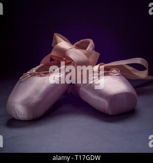 Le ballet des chaussons chaussures de danse avec un arc de rubans joliment pliées sur fond sombre Banque D'Images
