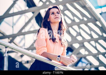 Entreprise à succès femme debout sur le balcon de l'office moderne et regarde au loin. Banque D'Images