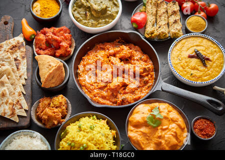 Divers plats indiens sur une table. Spicy chicken Tikka Masala dans la poêle de fer. Servi avec du riz, épices et naan. Ensemble d'autre genre nourriture indienne.