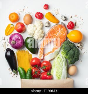 Supermarché. Sac de papier plein d'aliments sains sur un fond blanc. Vue d'en haut. Mise à plat. Banque D'Images
