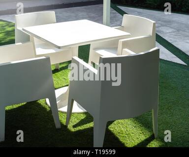 Des chaises en plastique vert et table en bois en face de la ...