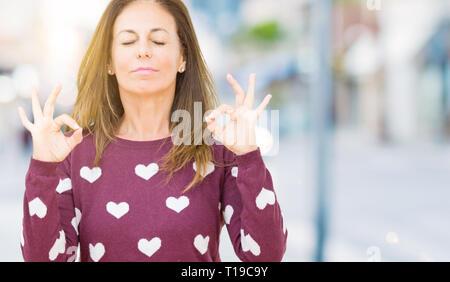 Belle femme d'âge moyen portant des cœurs isolés plus chandail contexte vous détendre et souriant avec les yeux fermé faisant le geste de la méditation avec les doigts. Y Banque D'Images