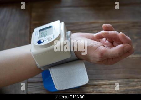 Femme d'âge moyen prend sa pression artérielle à domicile Banque D'Images