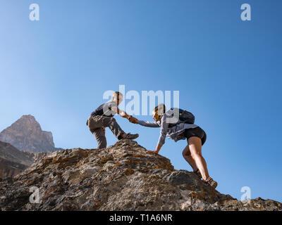 Coup de main couple les randonneurs en montagne