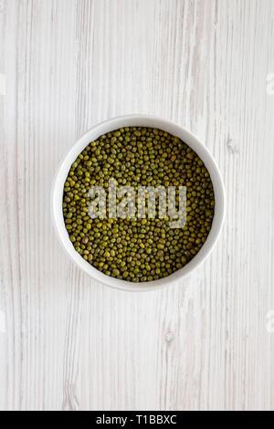 Les haricots mungo vert dans un bol blanc gris sur fond de bois, vue du dessus. Mise à plat, les frais généraux, d'en haut. Banque D'Images