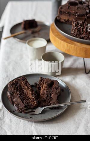 Morceaux de gâteau au chocolat sur la plaque grise, gâteau sur support en bois, verre de lait sur la table. Concept de dessert table set Banque D'Images