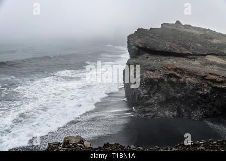 Les falaises et les vagues sur Kirkjufjara beach en Islande sous un ciel couvert, jour brumeux. Banque D'Images
