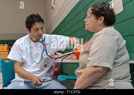 Un infirmier prend la pression artérielle d'une femme d'âge moyen dans un programme d'approche communautaire. Banque D'Images