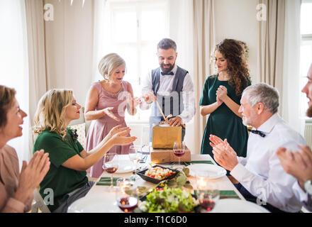 Un homme mûr avec des amis et de la famille présente l'ouverture sur une fête d'anniversaire. Banque D'Images