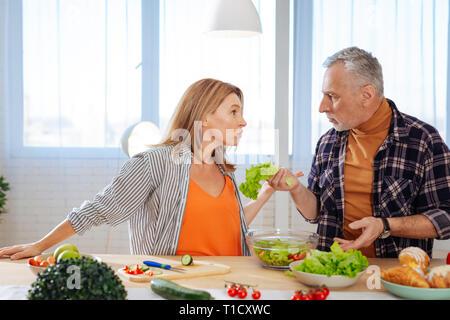 Couple having argument émotionnel pendant la cuisson salade pour le déjeuner Banque D'Images