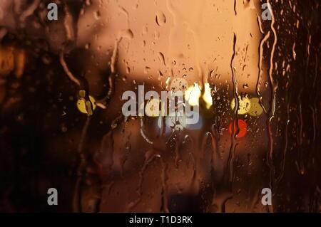 Sunset glow eau gouttes sur la fenêtre Banque D'Images