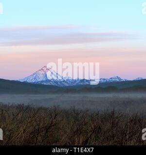 Vue sur le volcan Vilyuchinsky sur le mornimg brumeux, péninsule du Kamchatka, en Russie. Banque D'Images