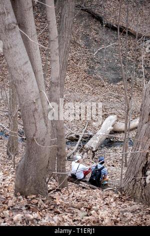 Deux hommes assis sur une planche à roulettes avec sac à dos par Shadow Falls Creek qui va dans la rivière Mississippi. St Paul Minnesota MN USA Banque D'Images