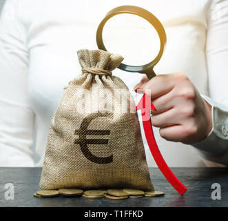 Femme main courante loupe sur sac d'argent et la flèche vers le haut. L'analyse de concepts de profits et de budget dans la société. Réussite de l'entreprise. L'ensemble, les