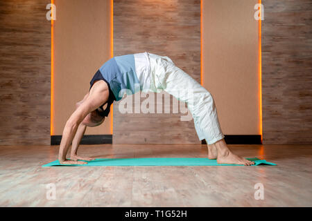 Hot man practicing yoga debout en posture de pont sur le tapis bleu. Banque D'Images