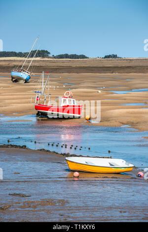 Bateaux colorés sur les bancs de sable à marée basse sur les marins de la flotte et de l'estuaire de la rivière au Wells next the sea, North Norfolk Coast, East Anglia, Angleterre, Royaume-Uni.