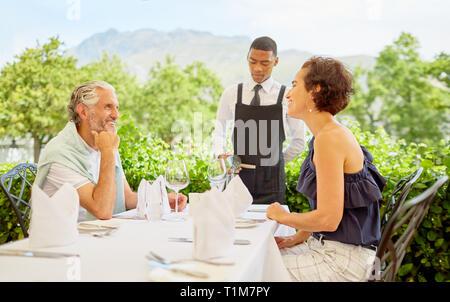 Verser le vin vins d'âge mûr pour un repas à table patio Banque D'Images