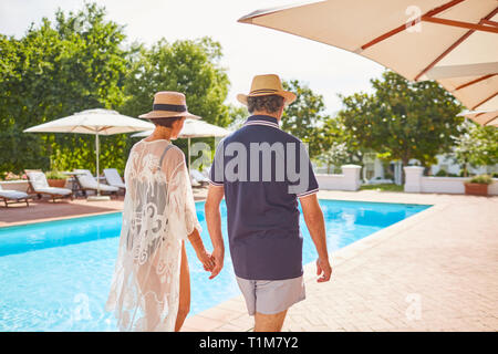 Young couple holding hands, marcher le long de sunny resort piscine Banque D'Images