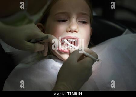 Peur petite fille à l'office, les dentistes dans la douleur lors d'un traitement. Les soins dentaires pédiatriques et la peur du dentiste concept.