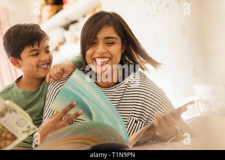 Happy mother and son reading books on bed Banque D'Images