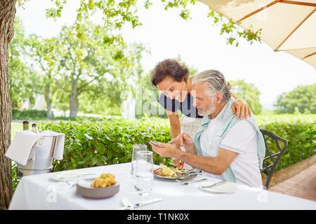 D'âge mûr, manger à l'aide de smart phone at table patio Banque D'Images