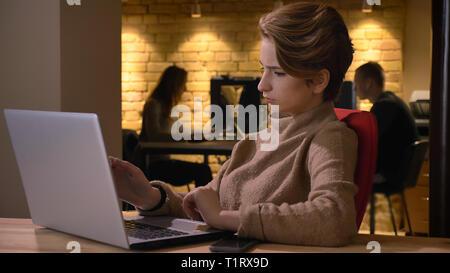 De jeunes pousses Gros plan belle caucasian businesswoman typing sur l'ordinateur portable et d'être pénalisé par un problème à l'intérieur dans le bureau