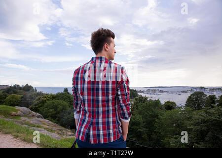 L'homme en costume élégant à l'avant à l'horizon de mer. Debout sur le haut de la roche. La Finlande, Helsinki, les îles. Banque D'Images