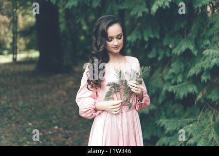 La féminité, agréable jeune fille dans une robe rose doux dans le parc par une chaude journée de printemps tenant un rameau d'un conifère cyprès Banque D'Images