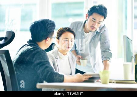 Trois jeunes dirigeants d'Asie qui travaillent ensemble à discuter du plan d'office. Banque D'Images
