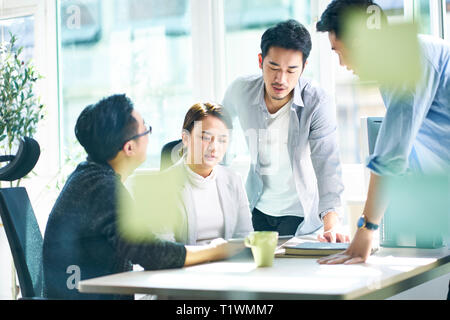 Groupe de quatre jeunes dirigeants de sociétés asiatiques meeting in office discuter affaires en bureau. Banque D'Images