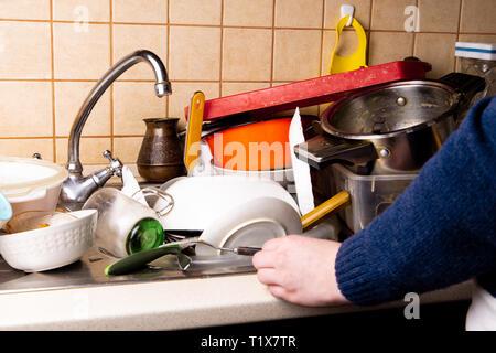 Fille main près de beaucoup de vaisselle sale dans l'évier de la cuisine que vous souhaitez nettoyer. Banque D'Images