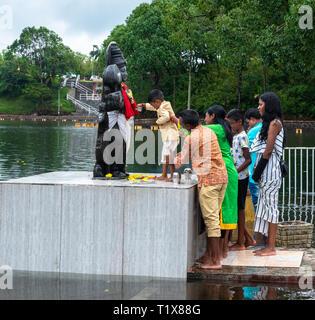 Grand Bassin, Maurice-21 janvier 2018. Les membres de la famille titulaires d'un jeune garçon stable comme il se dresse sur un autel et fait une offrande à un dieu hindou. Banque D'Images