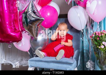 Cute little baby girl en fête robe rouge assis sur une chaise entre les ballons roses et fleurs, smiling and holding smartphone dans sa main, sur Banque D'Images