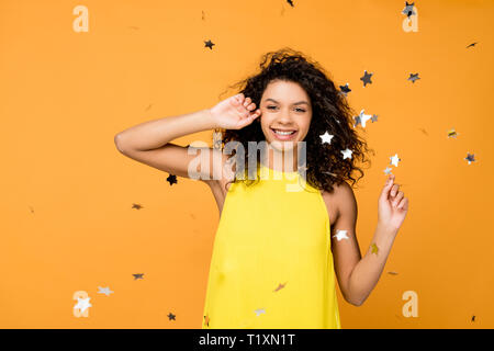 Curly african american woman in robe jaune brillant sourire près de confettis étoile sur l'orange Banque D'Images