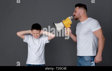 Des problèmes familiaux. Père en colère avec mégaphone de crier sur son fils, qui fermer les oreilles et le strabisme, l'arrière-plan sombre studio Banque D'Images