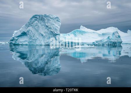 Un iceberg étonnant dans le cimetière de glace en Antarctique, provoquant une belle réflexion sur la surface de l'eau alors que dans un zodiaque Banque D'Images