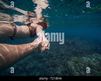 Young couple holding hands tout en apnée sur un récif dans l'eau turquoise Banque D'Images