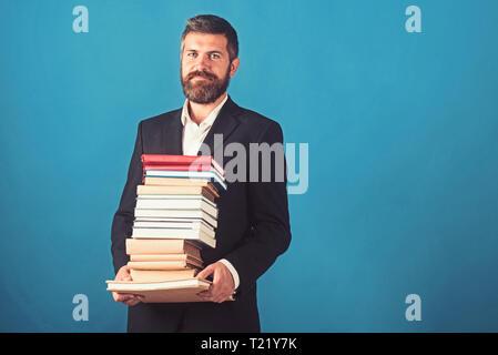 Businessman with pile of books sur fond bleu. Leçon de la littérature et de la lecture livre. Le temps de l'école enseignant en bibliothèque universitaire. Dans l'éducation Banque D'Images