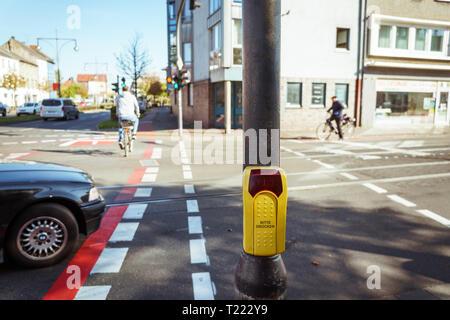 Bouton de passage pour piétons avec des personnes floues de traverser la route au passage protégé pour piétons, fermer en jaune bouton de passage dans la rue en Allemagne, Krefeld. Banque D'Images