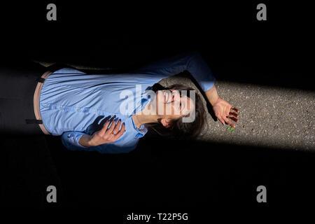 Laughing young woman lying entre ombre et lumière du soleil sur la rue Banque D'Images