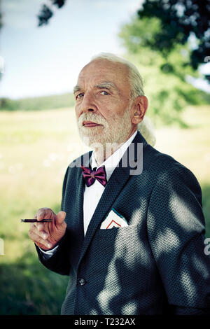Portrait of senior man wearing suit coat, noeud papillon et pochette dans la nature de fumer un cigarillo Banque D'Images