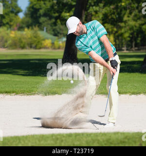 Golfeur frappe la balle hors de fosse de sable. L'accent sur golfeur, boule de sable dans la vague de flou.