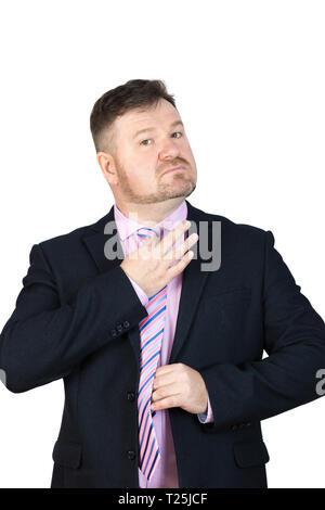 Un gros homme d'âge moyen avec une barbe se redresse sa cravate autour de son cou. Banque D'Images