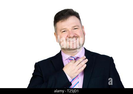 Un gros homme d'âge moyen avec une barbe se redresse sa cravate autour de son cou fond isolé. Banque D'Images