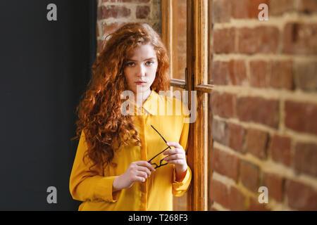 Fille rousse bouclée dans la chemise jaune holding glasses près de la fenêtre dans la placement loft Banque D'Images