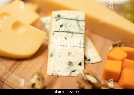 Assortiment de fromages sur le plateau de la carte en bois rond Camembert, fromage à pâte dure, tranches de noix