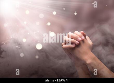 Dans les mains des hommes priant avec ray position sur l'arrière-plan flou Banque D'Images