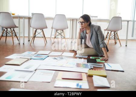 Full Length portrait of smiling businesswoman sitting on floor in office lors de la planification de projet , copy space Banque D'Images